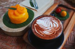 Nice Texture of art on hot coffee with orange cake.  royalty free stock photography