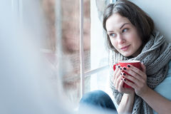 Nice thoughtful woman looking through the window royalty free stock photography