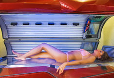 Nice time. Posing beautiful girl in swimsuit  at solarium Royalty Free Stock Photography