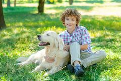 Nice time with a golden retriever. For one lovely redhead boy sitting on the green grass in the park. Positive emotions of an animal and a human stock images