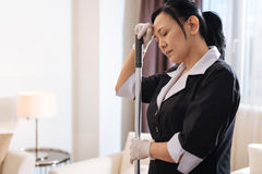 Nice tired chambermaid holding her forehead Royalty Free Stock Images