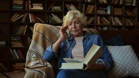 Nice tired senior woman reading a book. Involved in thoughts. Concentrated pleasant elderly woman sitting in the arm chair and reading a book while feeling tired stock video