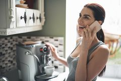 Happy girl answering call in kitchen. Nice to hear you. Smiling beautiful woman standing by coffee machine and preparing hot drink. She is holding mobile and royalty free stock photography
