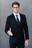 Nice to meet you at our company!. Cheerful young businessman stretching out hand for shaking while standing against grey background Royalty Free Stock Image