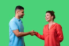 Free Nice To Meet You! Portrait Of Happy Young Couple In Casual Wear Shaking Hands. Isolated On Green Background Stock Photo - 163464400