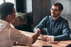 Nice to meet you! Young modern men in smart casual wear shaking. Hands and smiling while spending time in the office stock photos