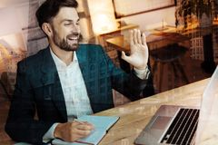 Cheerful businessman greeting his interlocutor through web camera. Nice to see you. Pleasant young businessman sitting at the table and waving at the web camera Royalty Free Stock Images
