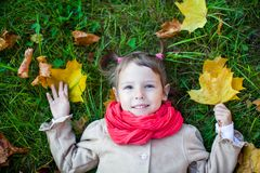 Nice toddler girl lying on the green grass. Small girl outdoor in the park with yellow leaves Stock Photo