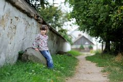 Nice toddler girl near the wall  on country road Stock Images