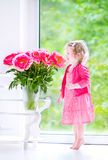 Nice toddler girl playing with peony flowers Stock Images