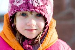 Nice toddler girl in winter pink hat. Nice toddler girl with blue eyes in winter pink hat looking into the camera stock photos