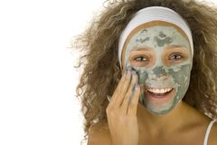 Nice in touch. Young woman putting on face green purifing mask. She's on white background. She's looking at camera Stock Image