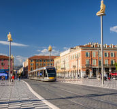 Nice tramway at Place Massena. NICE, FRANCE - OCTOBER 2, 2014: Nice tramway entering Place Massena, the main pedestrian square of the city. Artworks surround the Stock Photography