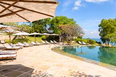 Nice tropical pool side with sun-loungers und sun umbrellas.  Stock Images