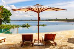 Nice tropical pool side with sun-loungers und sun umbrella.  Royalty Free Stock Images