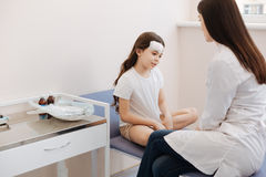 Nice unhappy girl talking to her doctor stock photo