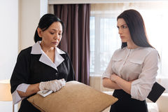 Nice unhappy hotel maid holding a cushion. I couldnt clean it. Nice sad unhappy hotel maid standing near her manager and holding a cushion while working in the stock photos