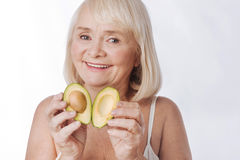 Nice verrukte vrouw die de twee avocadohelften samenbrengen stock fotografie