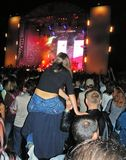 Nice view. Concert at night. Big crowd. Girls sit on boys to see the stage Royalty Free Stock Images