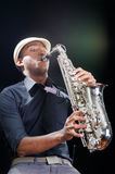 A nice view from below, black man is playing the saxophone. Professional hands with white hat Stock Images
