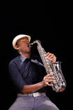 A nice view from below, black man is playing the saxophone. Professional hands with white hat Stock Photography