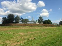 Nice view on the church. Summer blue sky people church field greens grass Royalty Free Stock Image