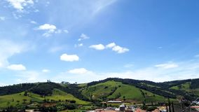 Green sunny mountains landscape, blue sky and white clouds, Motion Lapse, Time lapse.Green sunny mountains landscape over a villag stock footage