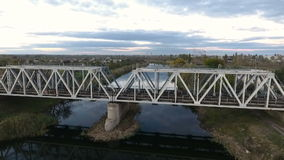 Nice view from the height on the railroad bridge, shooting a drone flying over the river with a view of the railway stock video