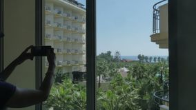 Nice view from the hotel window on the sea, palm trees. The girl takes a photo of the landscape from her room. 4k stock footage