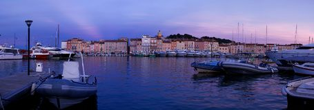 Saint Tropez Houses on the Yacht Harbour After Sunset. A nice view on the houses built around the yacht port of Saint Tropez, after sunset, with some boats in Royalty Free Stock Image