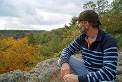 Nice View. A man sits at the top of a hill and enjoys the view Royalty Free Stock Photography