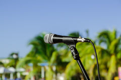 Nice view of microphone on stand in outdoor tropical garden against blue sky background Stock Photo