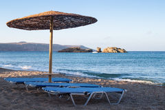 Nice view on the seaside. Straw parasol and sunbeds on the shore Royalty Free Stock Images