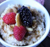 A nice warm bowl of oatmeal, topped with raspberries and blackberries with walnuts and drizzle of maple syrup.  royalty free stock photos