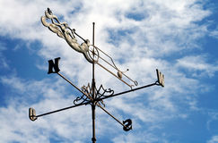 Nice weather vane. Weather vane against a cloudy blue sky royalty free stock photos
