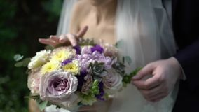 Nice wedding bouquet in bride`s hand. Hands of the bride and groom with rings on a beautiful wedding bouquet stock footage