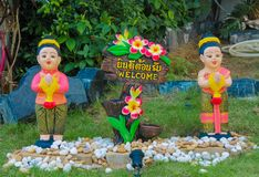 Nice welcome figure in asian tropical garden. Nice funny colorful welcoming figures of smiling boy girl and animal in asian pagoda garden Royalty Free Stock Images