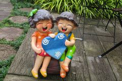 Nice welcoming colorful figure in asian garden. Nice funny colorful welcoming figures of smiling boy girl and animal in asian pagoda garden Royalty Free Stock Images