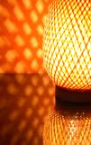 Nice Wicker Desk Lamp. Nice wicker glowing desk lamp with reflection against red wall Stock Images