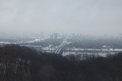 Nice winter landscape. Morning in city. Metro bridge connects the two banks of the city. Road goes for horizon. Buildings are hidi Royalty Free Stock Photo