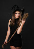 The  nice witch with a broom in the studio Stock Images