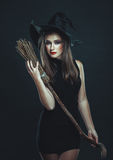 The nice witch with a broom in studio Stock Photography