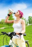 Nice woman biker drinking Stock Photography