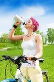 Nice woman biker drinking Stock Photography