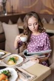 Nice woman eat breakfast in cafe. Reading a magazine. Portrait of young charming female drinking coffee and eat eggs stock photo