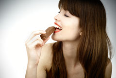 Nice woman eating a bar of chocolate - studio shot Stock Photography