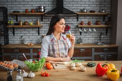 Nice woman enjoy drinking wine in kitchen at table. She look to right and smile. Colorful vegetables on table. Nice woman enjoy drinking wine in kitchen at royalty free stock photos
