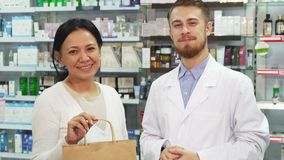A nice woman gets a bag with her purchases. A women is standing in a drugstore and tells the pharmacist something. He listens to her attentively. Then he gives Royalty Free Stock Photography