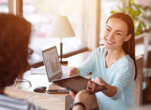 Nice woman holding tablet. Take it. Pleasant positive charming women sitting in the office and giving tablet to her colleague while expressing gladness royalty free stock image