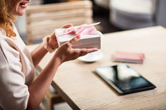 Nice woman holding wonderful present. Happy birthday to me. Cropped picture of cute woman sitting at the table while holding a box with gift Royalty Free Stock Image
